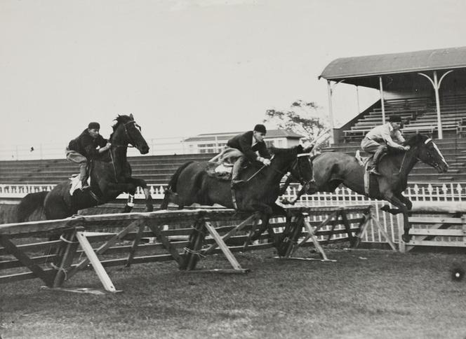 1940 Three jockeys jumping horses over fences at early morning training, Ellerslie.jpg